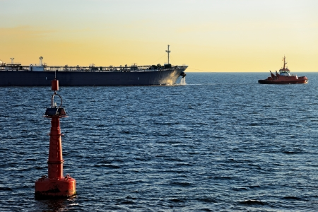 outbound: Red buoy on the fairway and outbound tanker in the sea