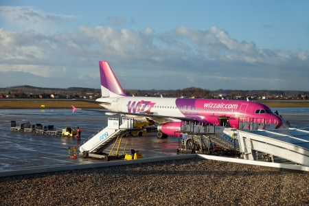 The Wizzair aircraft with staircase and people with cargo trolley and ground crew briefing to get ready for the next flight in Gdansk Airport, Poland. Photo taken on: January 13th, 2012 報道画像