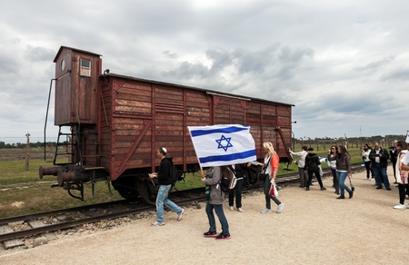 Auschwitz II-Birkenau, a former Nazi extermination camp in Poland. Israeli youth with flags at rail car that transported the prisoners to inside the camp. Photo taken on: August 15th, 2012