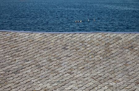 Red clay tiles roof pattern on sea background  photo