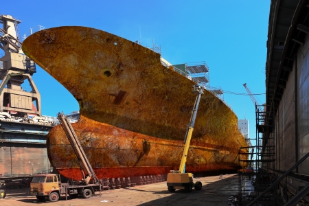 Workers sandblasting a large cargo ship from rust and corrosion.  Editorial