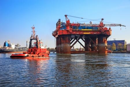 Ölbohrinsel in der Gesellschaft von einem Schlepper in einen Hafen