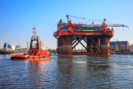 Oil rig in the company of a tug boats enters a port