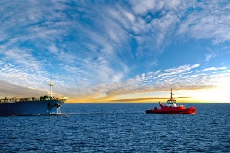 towed: Tanker at sea towed by tug