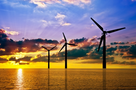 Silhouette of wind power stations over the sea at sunset  photo