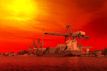 The Container Ship under loading in the harbor at sunset  photo