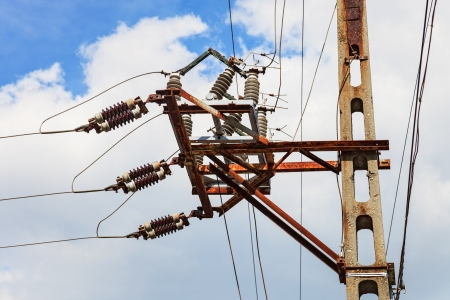 isolators: Electric pylon with isolators a rusted steel support bar  Stock Photo