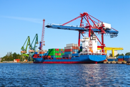 trading board: Seaport crane and huge container cargo ship ready for unloading