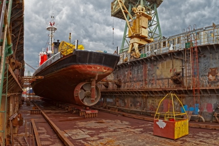 dockyard: Ship for repairs in large floating dry dock