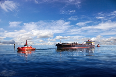 Tanker ship being guided into port by two tugs  photo