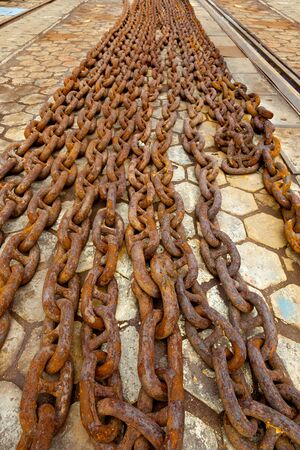a big ship: Steel anchor chains caked with rust at an shipyard  Stock Photo