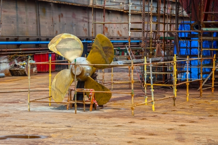 The propeller of a vessel in a dry dock being prepared for maintenance works