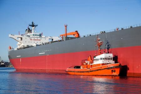 escorted: A orange tugboat assisting a large oil tanker
