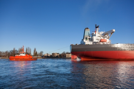 A orange tugboat assisting a large oil tanker  photo