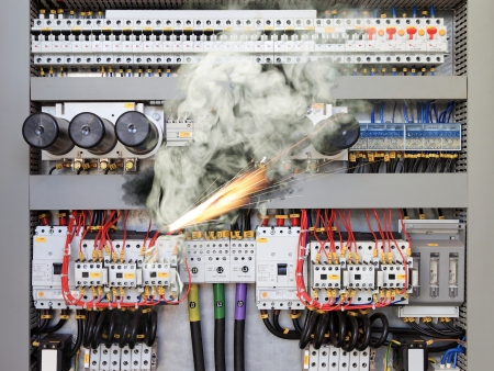 causing: Overloaded electrical circuit causing electrical short and fire  Stock Photo