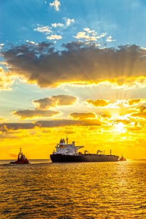 tug boat: Tug boat pulling the tanker ship at sea  Stock Photo