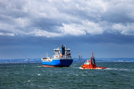 tug boat: Tanker ship is assisted by a tug boat in the port