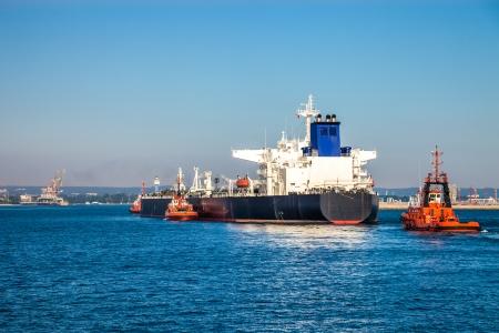 tug boat: A huge oil tanker and tugboats at work
