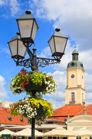 Flower arrangement on street lamp in the background the town hall in Bialystok, Poland  photo