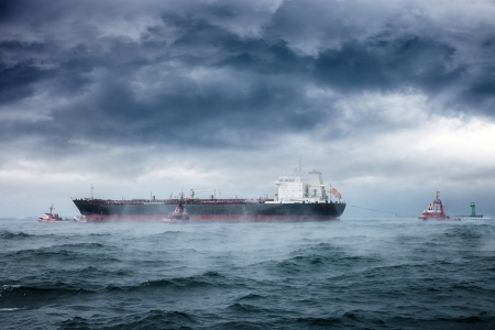 Dark image of tanker and tugboats on sea during a violent blizzard
