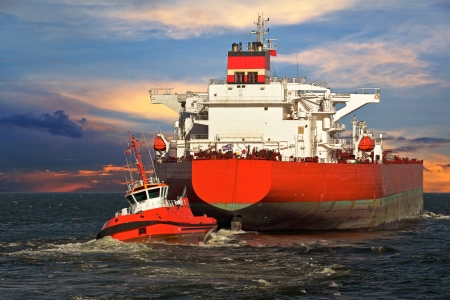 marine industry: Tug boat towing a tanker ship at sea  Stock Photo