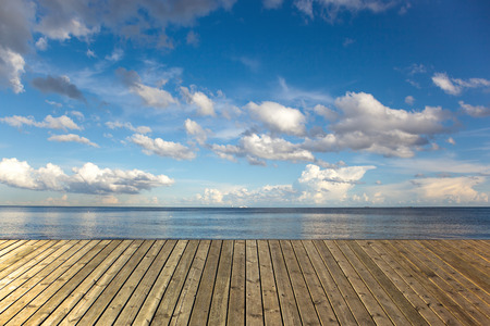 Empty wooden pier on a sea with blue sky and clouds  photo