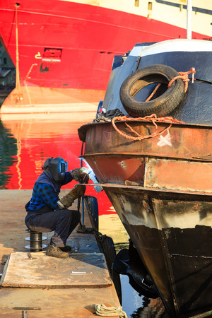Welder in a protective mask when welding the hull of the ship  photo