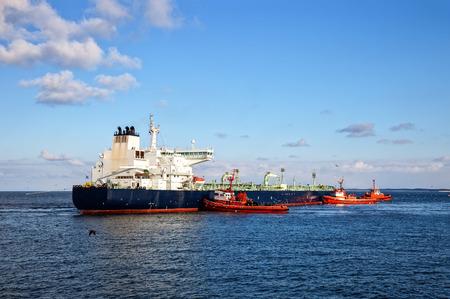 tug boat: A huge oil tanker and three tugboats at work