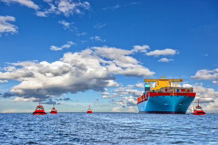 Tugboat assisting container cargo ship to harbor  Stock Photo
