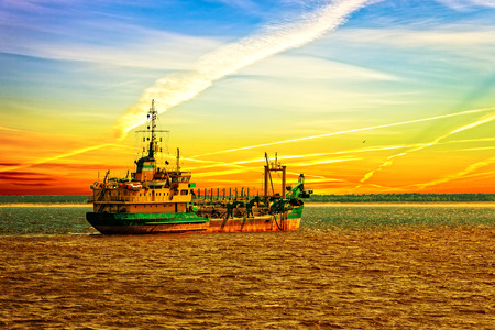 Dredger ship working in the port at sunset   photo