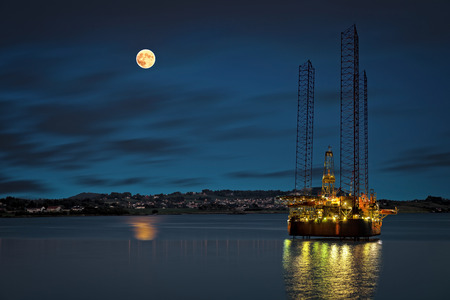 Oil platform at night time and the moon   photo