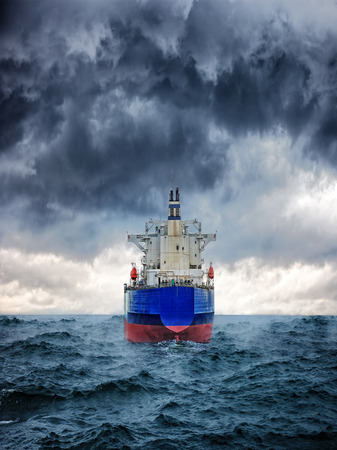 Dark image of big cargo ship in strong storm  photo