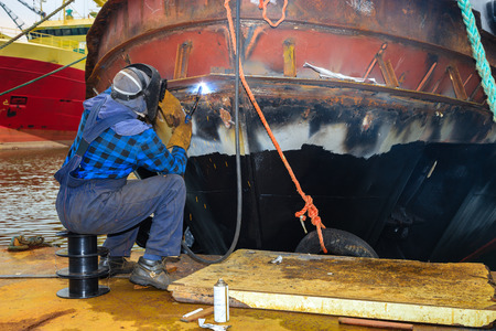 Welder in a protective mask when working. photo