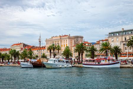 Tourists walk on Split sea promenade flanked by lush palms.