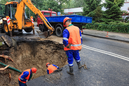 rupture: Workers repairing the damaged road - rupture of the pipeline