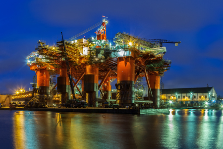 sea port: Oil Rig in the shipyard for maintenance at night.