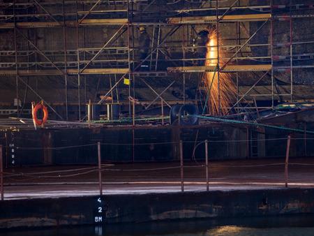 A shipyard steel worker burning steel on scaffolding. photo