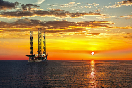 Oil drilling rig in sunset time.