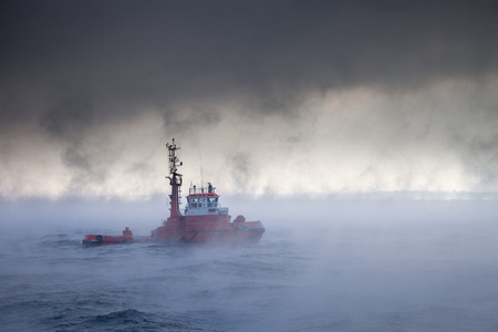 Dark image of ship on sea during a violent blizzard photo