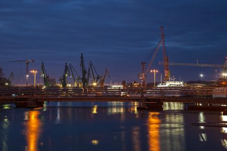 Big cranes and bridge at the shipyard at night.