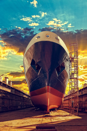 Ship in dry dock at sunrise - shipyard in Gdansk, Poland.