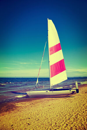 A colorful sailboat on a sand beach. Vintage toned photo.