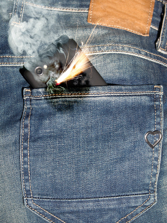 Close up of burning phone in jeans back pocket. photo