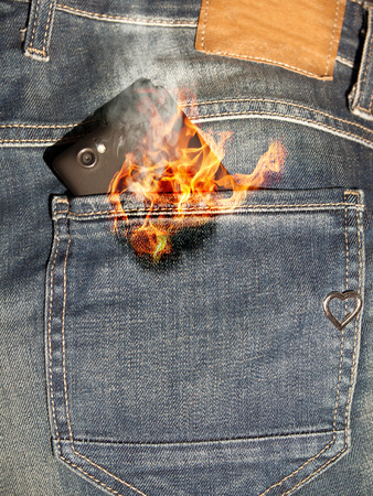Close up of burning phone in jeans back pocket.