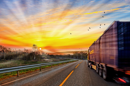 containers: Truck traveling on road at sunrise - speed and delivery concept.