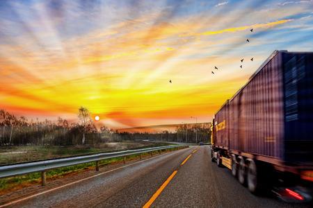 Truck unterwegs auf der Straße bei Sonnenaufgang - Geschwindigkeit und Lieferkonzept.
