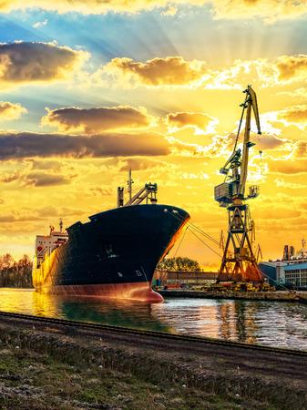 Frachtschiff und Hafen bei Sonnenuntergang.