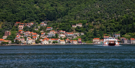 View of Boka Kotorska with pier and boats in Lepetance, Montenegro. photo