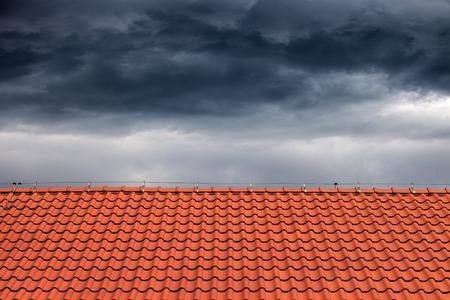 Dunkle Wolken regen über dem orangefarbenen Dach.