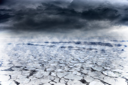 rain weather: Winter seascape with dark clouds over frozen sea.